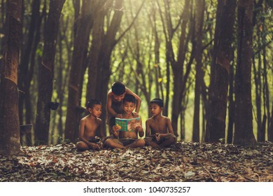 Rural children are reading a book at the forest.Book knowledge is important for Genes in the rural areas of Asia.