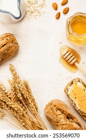 Rural or country breakfast - bread rolls, honey jar, milk, nuts, wheat and rolled oats on white wood from above. Background layout with free text space.