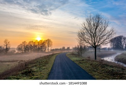 Rural country road in autumn morning sunrise. Rural road in morning sunrise. Early morning rural road sunrise landscape. Road in early morning sunrise