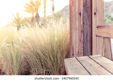 rural country space place with handmade wooden bench and gazebo with golden cereals field background in end of summer season