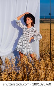Rural Countryside Scene. Young beautiful woman with long hair dressed in white Polka-dot dress and black hat standing at golden oat field with a white curtain on the background.