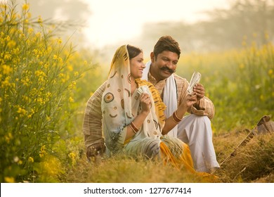 Rural couple holding Indian rupee notes in agriculture field