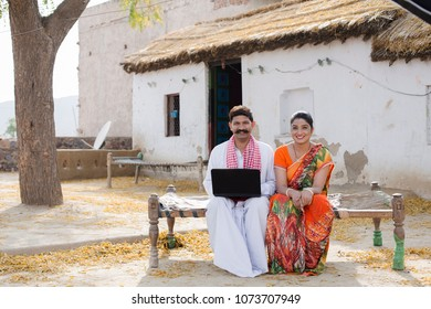 A Rural couple sitting on the cot with laptop.