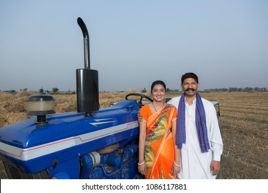 Rural Couple Standing Together Near Tractor