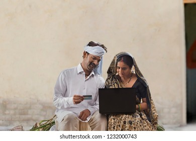 Rural couple using laptop and credit card doing online banking