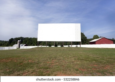 Rural drive-in screen in field with barn and blue sky. Horizontal.