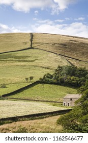 Rural England scene with fields separated by dry stone walls and a stone farm building on a hillside in the Peak District, UK
