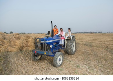 Rural Family sitting on a Tractor