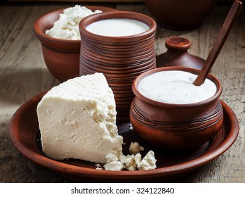 Rural farm dairy products: milk, sheep's cheese, cottage cheese in pottery in an old rustic background, selective focus