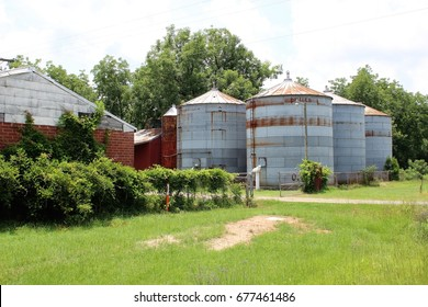 Rural farm land in small town Georgia with wood barn and rusted metal silos