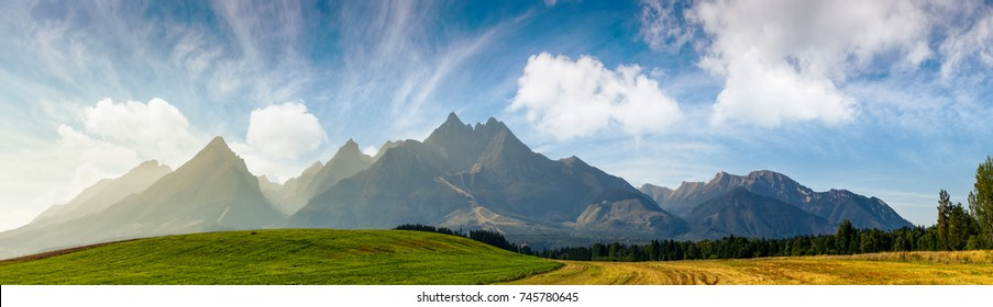 rural fields near Tatra Mountains in summer time. beautiful panorama of agricultural area. gorgeous mountain ridge with high rocky peaks