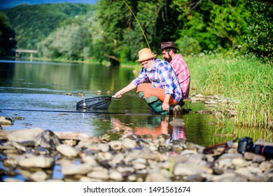 rural getaway. retired dad and mature bearded son. Two male friends fishing together. fly fish hobby of men in checkered shirt. retirement fishery. happy fishermen friendship. Catching and fishing.