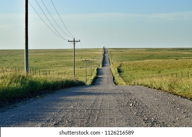 Rural gravel road lined with telephone poles going into distant open prairie in Oklahoma