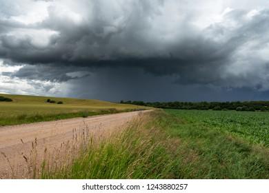 Rural gravel road under stormy summer clouds.