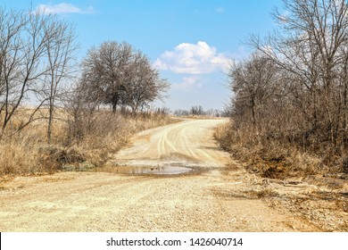 Rural gravel-dirt road in winter with mud puddle stretching across low spot and bare trees against blue sky