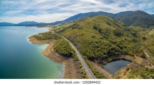 Rural highway along Tumut River coastline and mountains. Blowering, NSW, Australia - aerial panoramic landscape