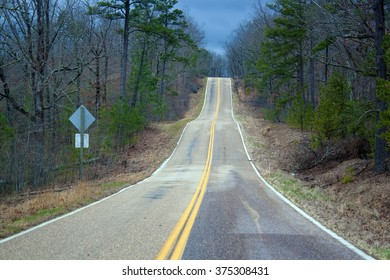 A rural highway under a cloudy sky.