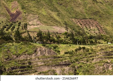 Rural hillside landscape with buildings, scrubs and trees along the road between Ambato and Banos in Tungurahua Province in Central Ecuador