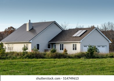 Rural House with a Roof-Mounted Solar Water Heater with a cloudless blue sky in the background.