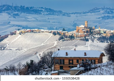 Rural house and sma;; medieval town on the hill with vineyards covered in snow in Piedmont, Northern Italy.