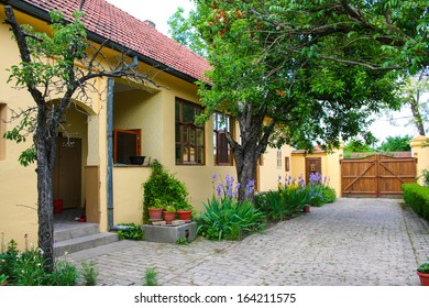 Rural household - house with front yard, flowers and gate.