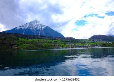Rural houses along Breinz lake with leaves of autumn at Interlaken, Switzerland.