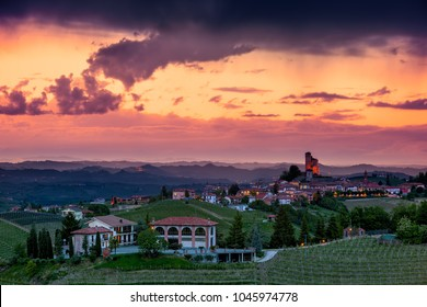 Rural houses on the hill with vineyards as small medieval town on background in evening in Piedmont, Northern Italy.