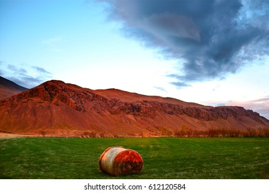Rural Icelandic landscaping and farm. Field with a bundle of hay in the foreground, in the background of the mountain in the light of the setting sun and the sky