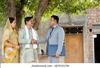 Rural Indian couple with farmer and bank executive shaking hands in village