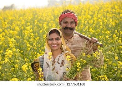 Rural Indian couple farming in agricultural field