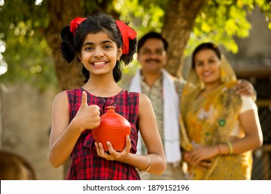 Rural Indian family with surprised daughter holding piggy bank