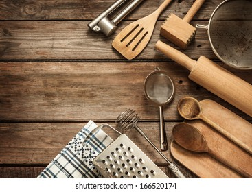 Rural kitchen utensils on vintage planked wood table from above - rustic background with free text space