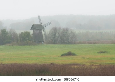 The rural landscape with a ancient windmill in the fog.
