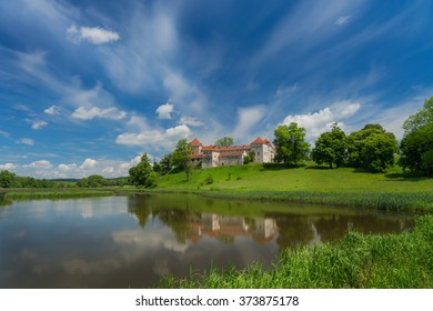Rural landscape with a castle in the Romanesque style with green hills, lake and blue sky with clouds