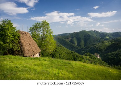 Rural landscape in the countryside hills of Transylvania, Romania in spring, with small isolated cottage with cane roof. Ecotourism