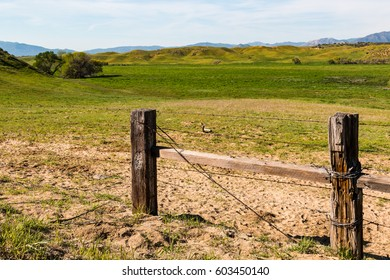 Rural landscape with fencing and rolling green hills and mountains.