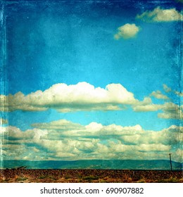 Rural landscape with flat road and power lines in foreground and mountain range in background under a cloud filled blue sky. Vintage grunge textured image with copy space.
