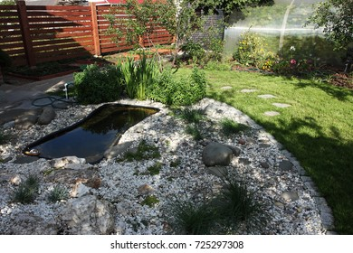 Rural landscape garden with a preformed plastic pond, rockery, lawn and flower bed in the sunny day