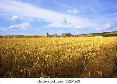 a rural landscape with golden wheat fields under a blue summer sky and a distant potash mine