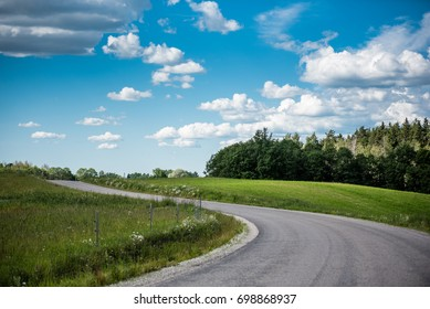 Rural landscape with green field, road and cumulus clouds in summer