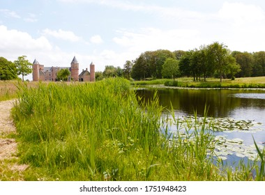 Rural landscape with a green park, a small lake and the medieval Westhove castle in the background