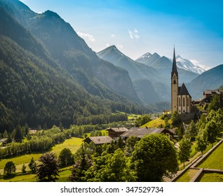 Rural landscape of Heiligenblut with St Vincent Church in Carynthia and Grossglockner (3797 m. elevation) highest mountain from Austria in background.