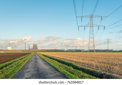 Rural landscape with a maize stubble field in the foreground with a row of tall high voltage pylons. In the background a power plant with a large concrete cooling tower and a smoking chimney.