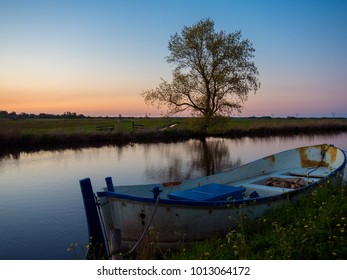 Rural landscape: old boat in a canal in the suburbs of Amsterdam at sunset with a solitary tree, Netherlands