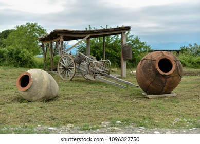 Rural landscape with old clay jugs and cart.