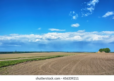 Rural landscape - plowed field with thunderclouds over them.