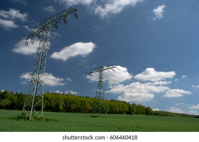 rural landscape with pylons and power lines and blue sky