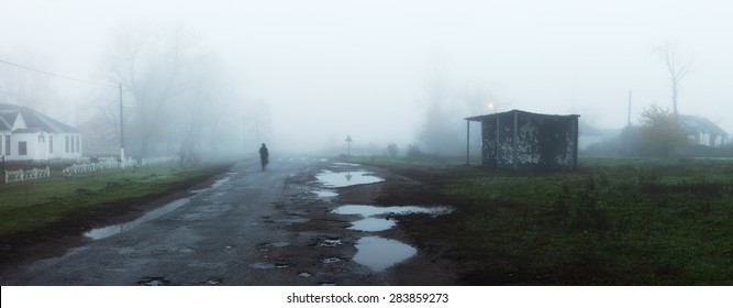 Rural landscape with road and bus stop in fog. Silhouette of man walking on misty village road. Loneliness, nostalgia, sad mood