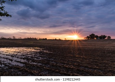 Rural landscape scene of sunrise sunset over a farm field after harvest. Sun breaks through clouds creating reflection in water standing in the field. Concepts of family farm, winter, after harvest