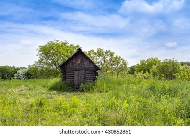 Rural landscape with a small old wooden house